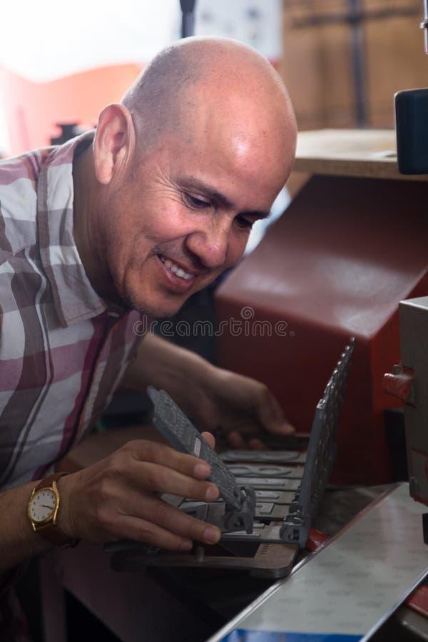 Homme supérieur faisant des nombres de véhicule sur la machine photo libre de droits