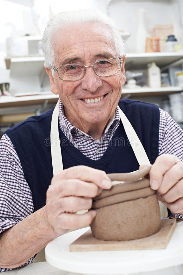 Homme supérieur faisant le pot de bobine dans le studio de poterie photographie stock
