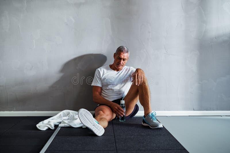 Homme supérieur fatigué détendant après une séance d'entraînement de club de santé image stock