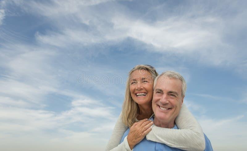 Homme supérieur ferroutant la femme contre le ciel nuageux photo stock