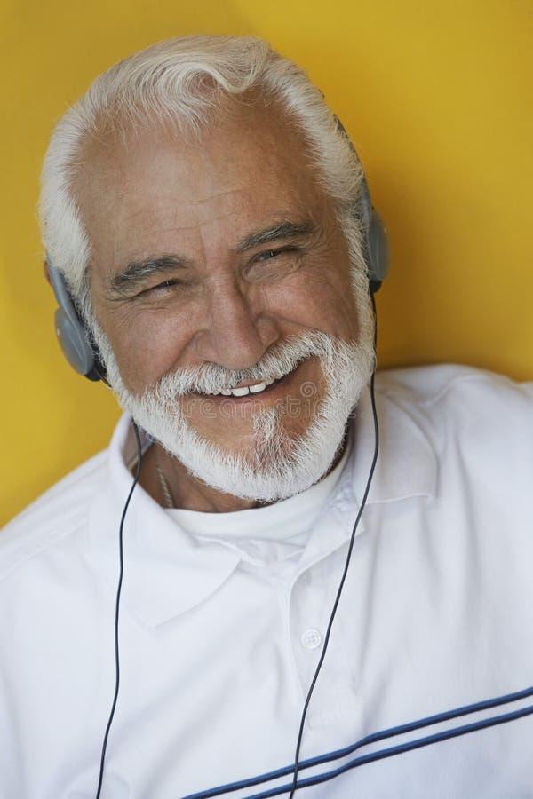 Homme supérieur heureux écoutant la musique par des écouteurs image stock