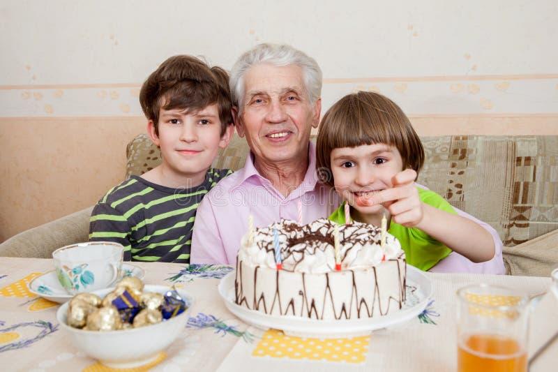 Homme supérieur heureux avec deux grandkids photographie stock