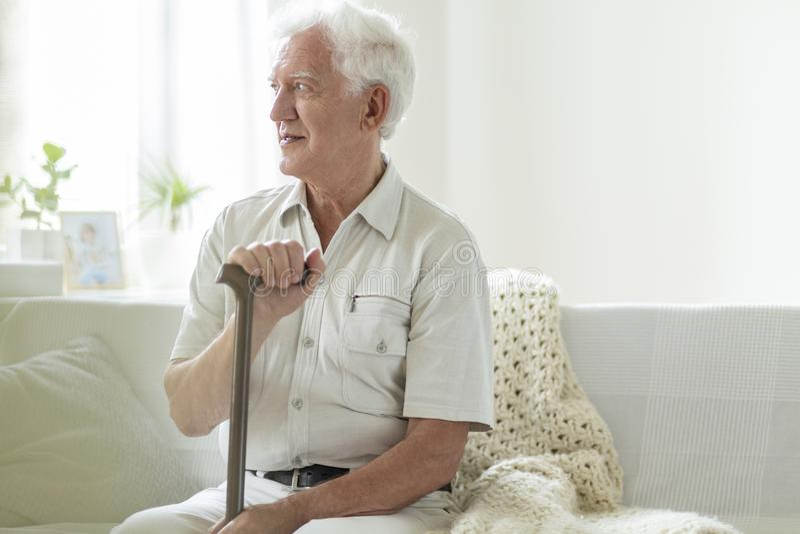 Homme supérieur heureux avec le bâton de marche détendant dans une maison de soins images stock