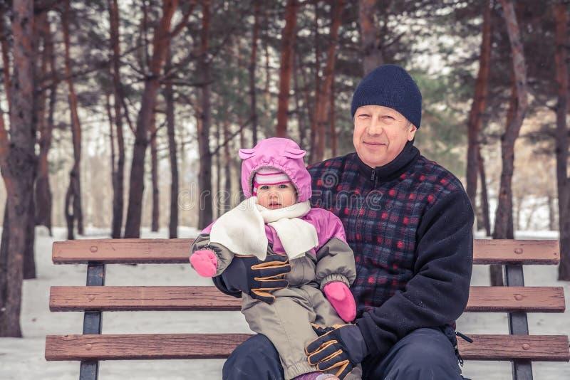 Homme supérieur heureux avec sa petite-fille s'asseyant sur le banc pendant la marche en parc d'hiver par temps neigeux pendant d photographie stock
