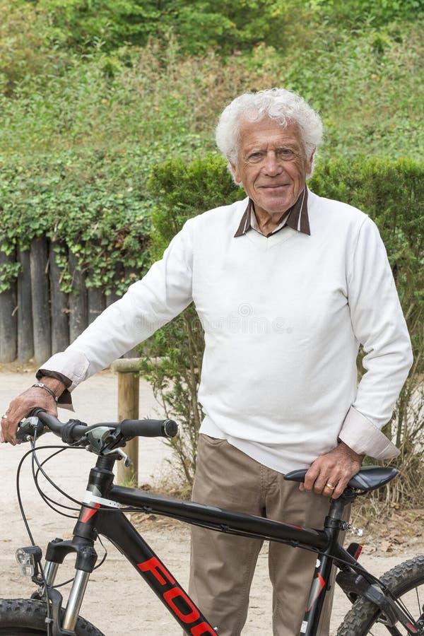 Homme supérieur heureux avec un vélo image stock