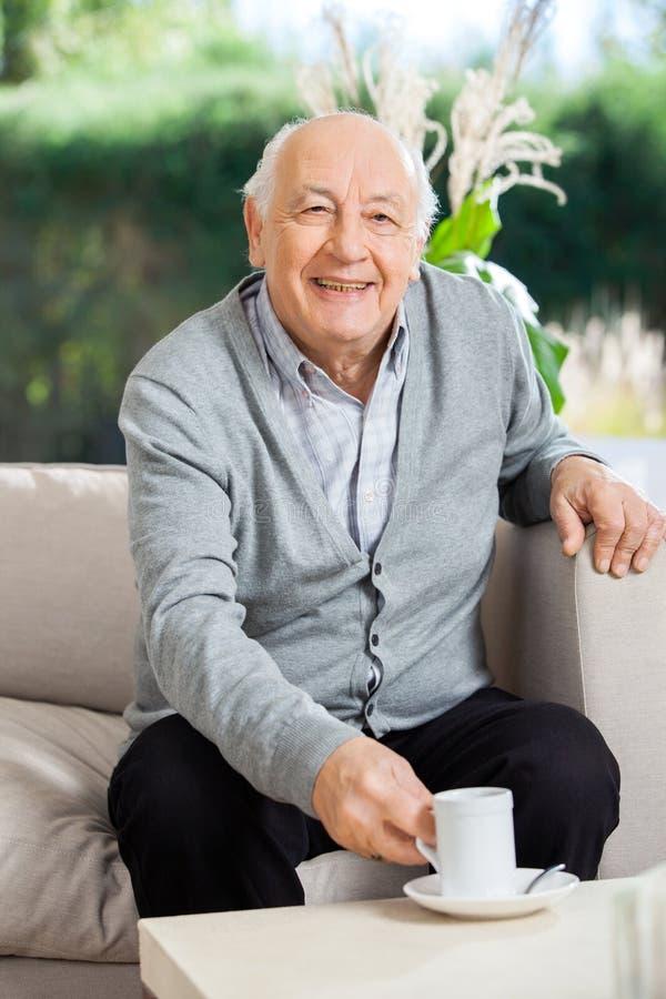 Homme supérieur heureux ayant le café à la maison de repos photographie stock