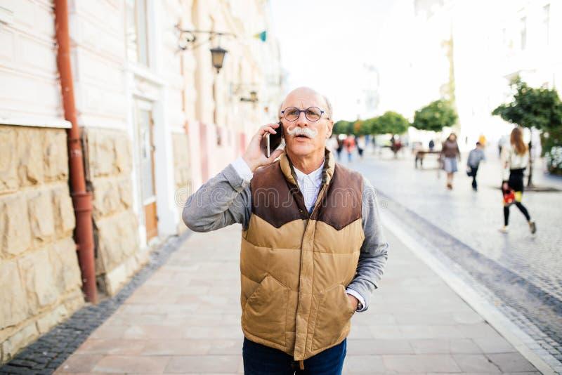 Homme supérieur heureux invitant le smartphone dans la ville photo stock