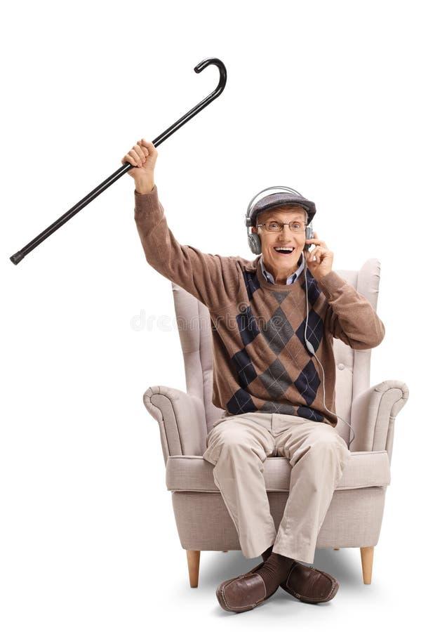 Homme supérieur heureux s'asseyant dans un fauteuil écoutant la musique sur des écouteurs et tenant une canne  photo libre de droits