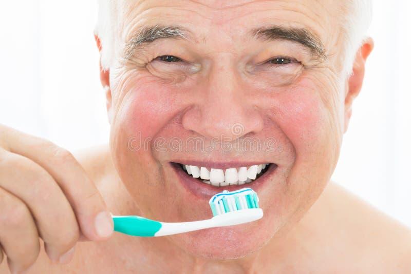 Homme supérieur heureux se brossant les dents photo stock