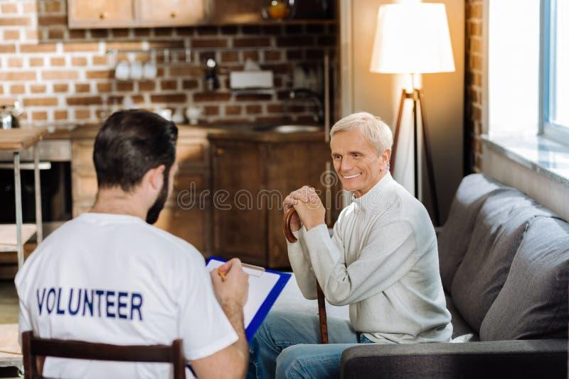 Homme supérieur heureux souriant tout en regardant le volontaire photo stock