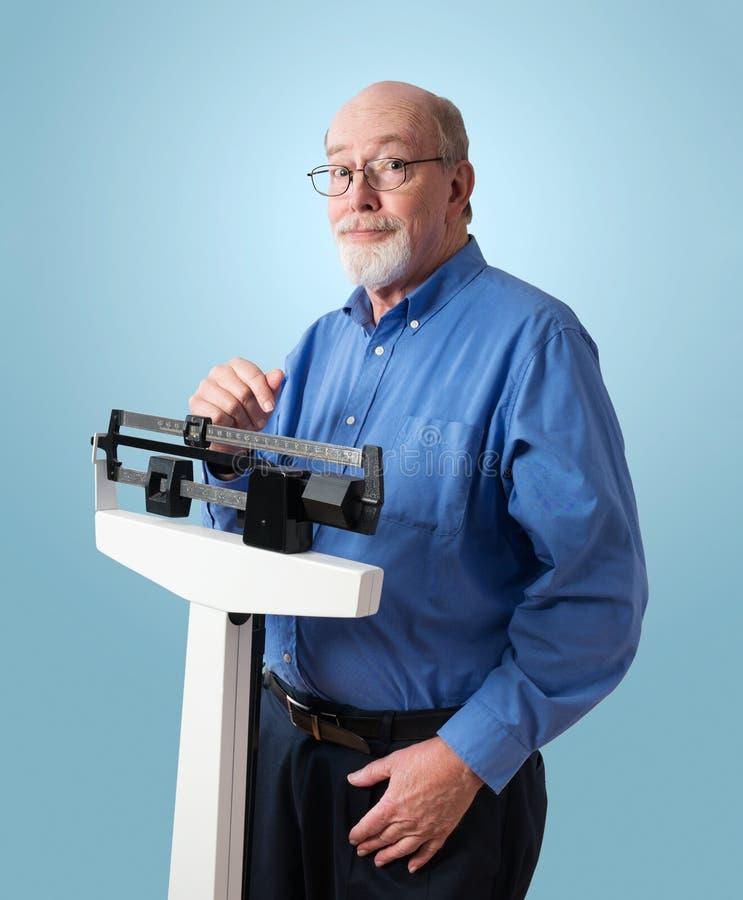 Homme supérieur heureux sur l'échelle de poids photo libre de droits