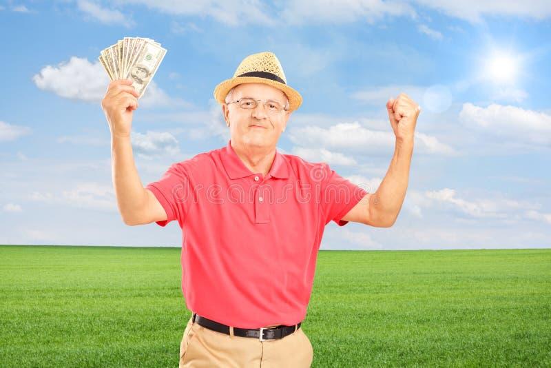Homme supérieur heureux tenant l'argent et faisant des gestes le bonheur sur un champ image stock