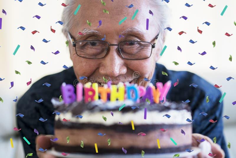 Homme supérieur heureux tenant le gâteau d'anniversaire images libres de droits
