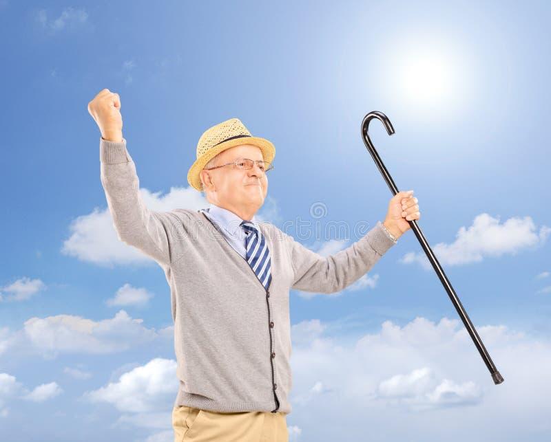 Homme supérieur heureux tenant une canne et faisant des gestes le bonheur dehors photo stock