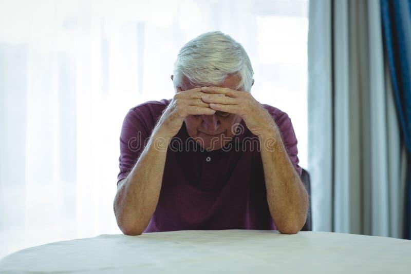 Homme supérieur inquiété s'asseyant dans le salon photo stock