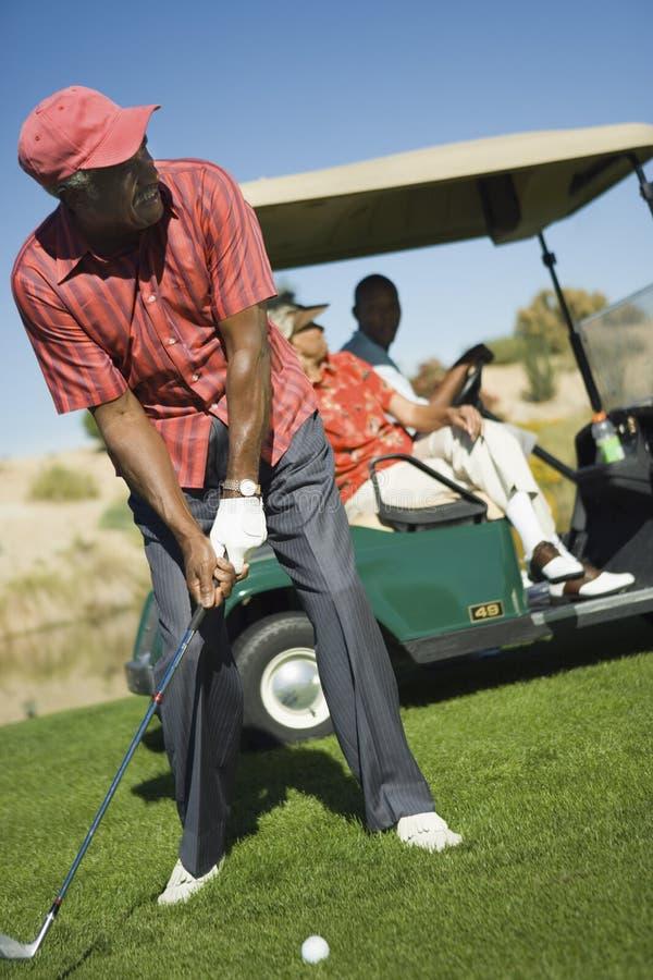 Homme supérieur jouant au golf photographie stock
