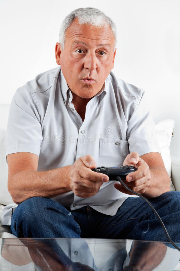Homme supérieur jouant le jeu vidéo image stock