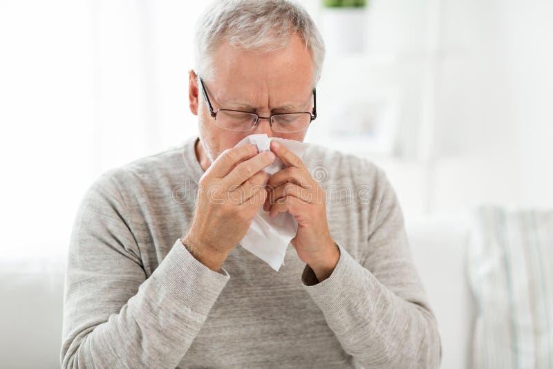 Homme supérieur malade avec le chiffon de papier soufflant son nez images stock