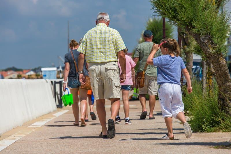 Homme supérieur marchant avec la jeune fille sur le trottoir images stock
