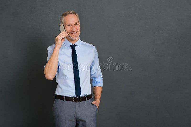 Homme supérieur parlant au-dessus du téléphone photographie stock