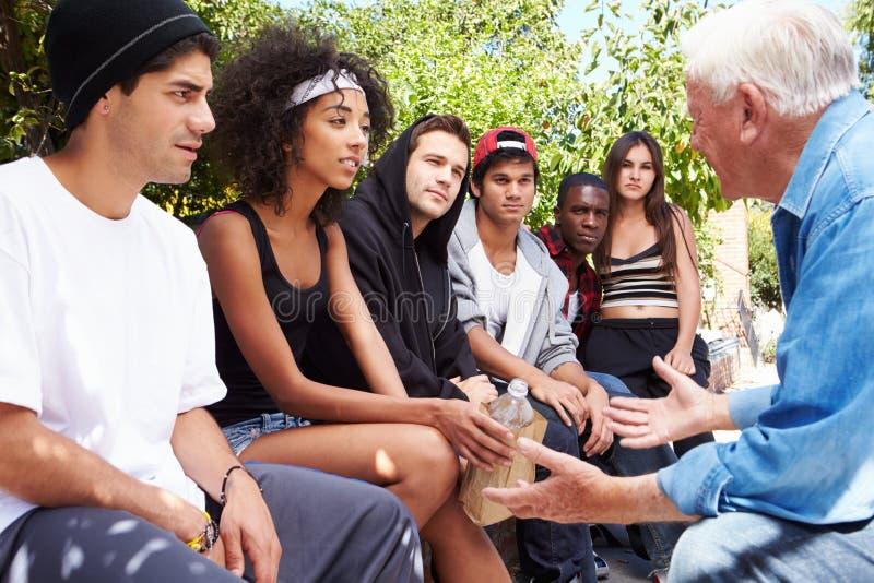 Homme supérieur parlant avec la bande des jeunes images stock
