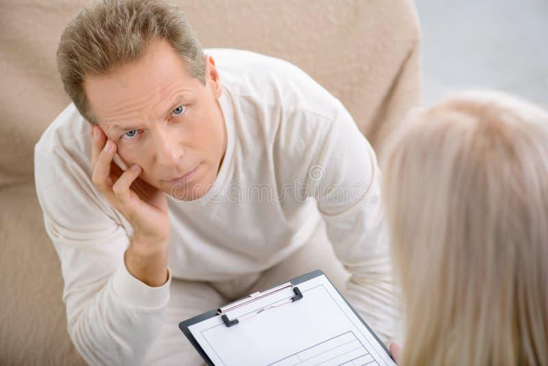 Homme supérieur parlant avec le psychologue photographie stock
