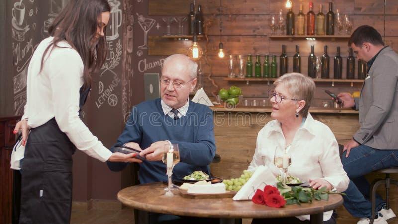 Homme supérieur payant le dîner à l'extrémité de la date avec une belle vieille dame photo libre de droits