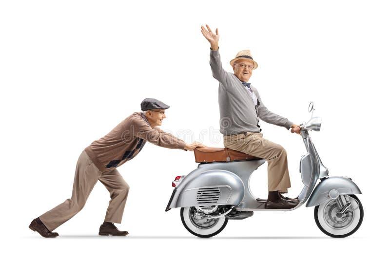 Homme supérieur poussant un monsieur supérieur montant un scooter de cru et ondulant à la caméra photographie stock libre de droits