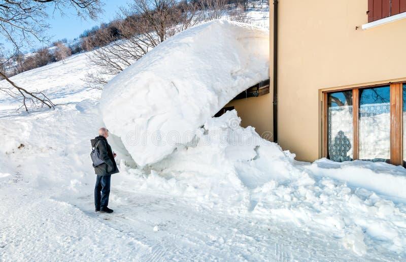 Homme supérieur près de l'entrée de la maison cachée sous la neige image libre de droits