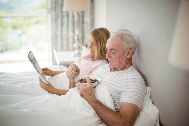 Homme supérieur prenant le petit déjeuner sur le lit images stock