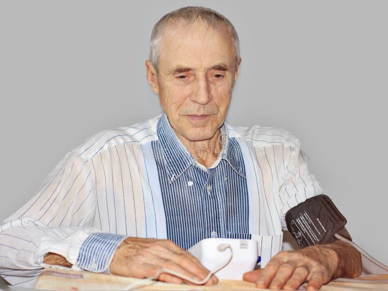 Homme supérieur prenant sa tension artérielle à la maison sur la table images stock
