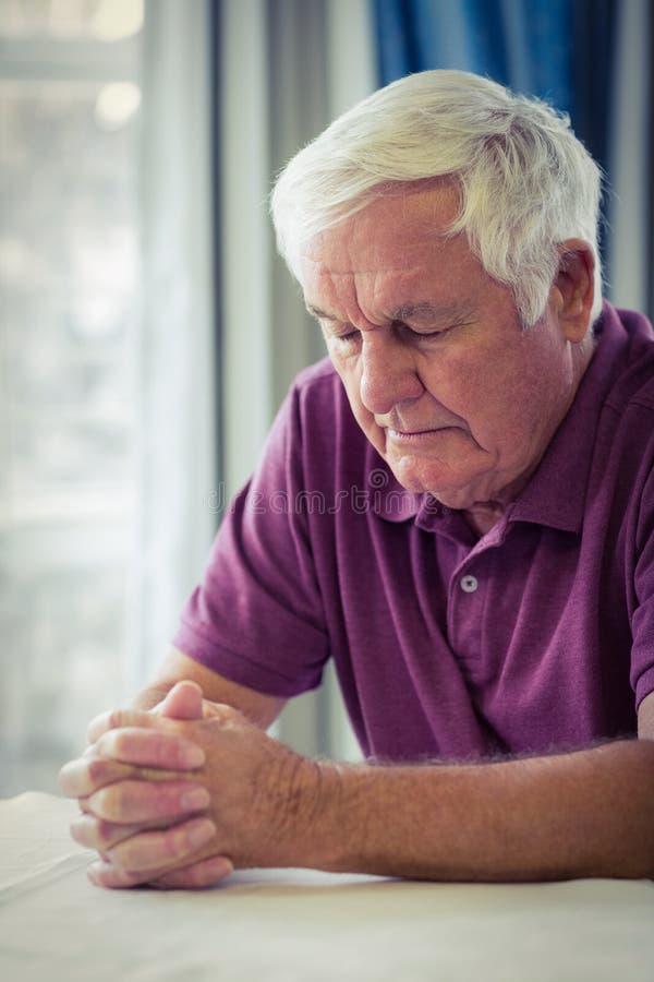 Homme supérieur priant dans le salon images libres de droits