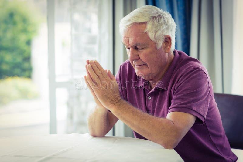 Homme supérieur priant dans le salon image libre de droits