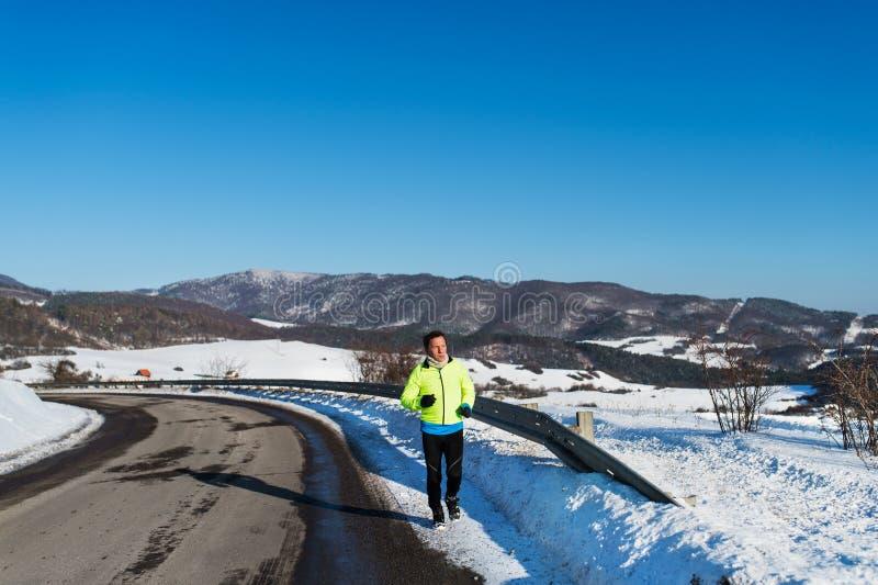 Homme supérieur pulsant sur une route en nature d'hiver Copiez l'espace photo libre de droits