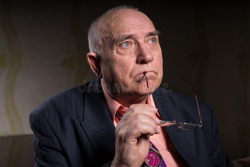 Homme supérieur réfléchi avec ses verres dans sa main image libre de droits