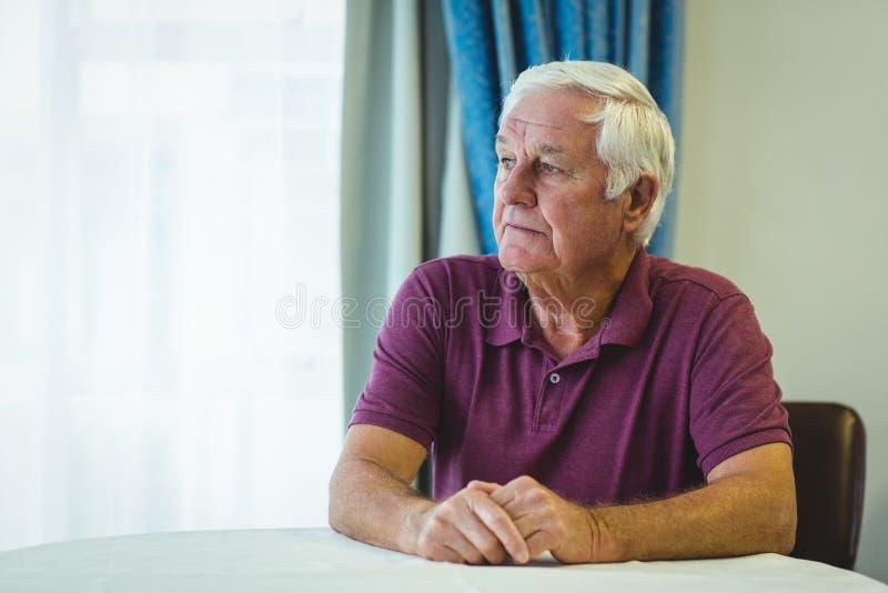 Homme supérieur réfléchi s'asseyant dans le salon photos libres de droits