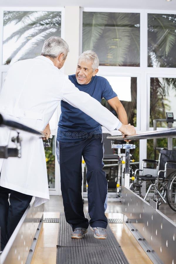 Homme supérieur regardant le centre de réadaptation de docteur While Walking In image stock