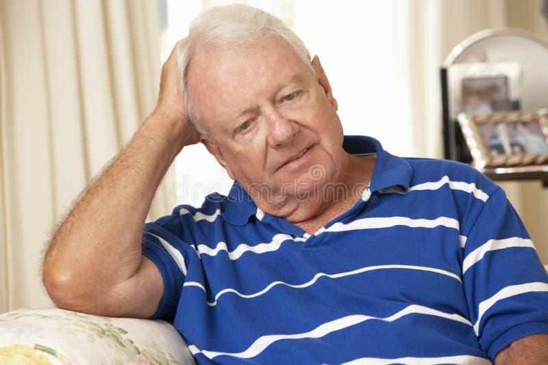 Homme supérieur retiré malheureux s'asseyant sur Sofa At Home image libre de droits
