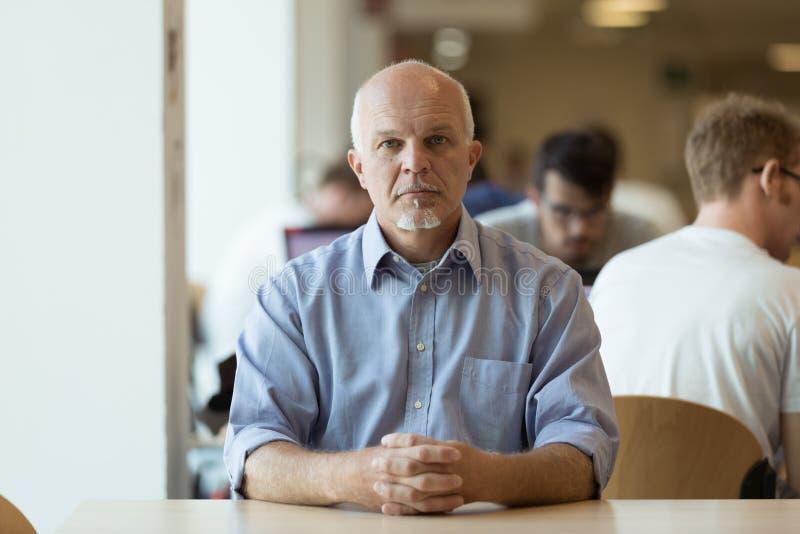 Homme supérieur sérieux seul s'asseyant dans un cafétéria photos libres de droits