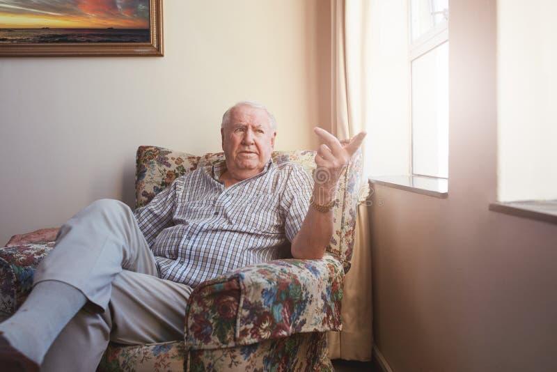 Homme supérieur s'asseyant à l'installation vivante aidée photo stock