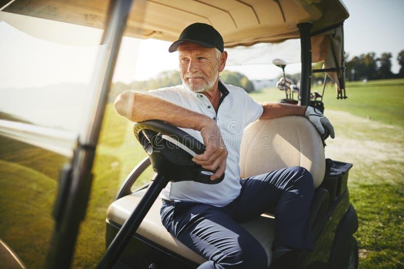 Homme supérieur s'asseyant dans son chariot de golf sur un fairway photo libre de droits