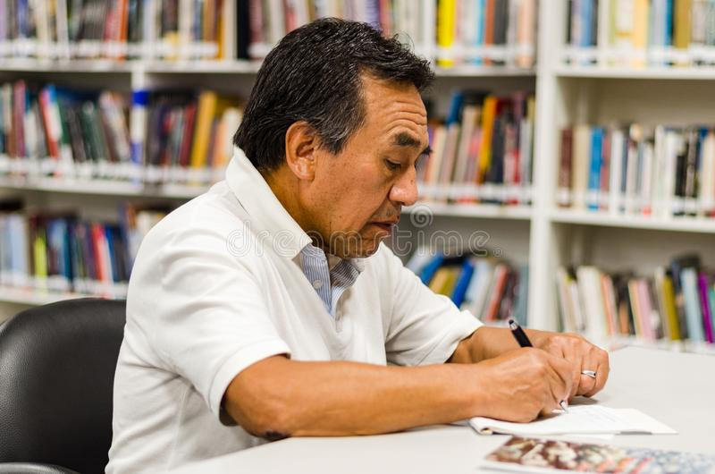 Homme supérieur s'asseyant dans une bibliothèque écrivant dans un bloc-notes images libres de droits