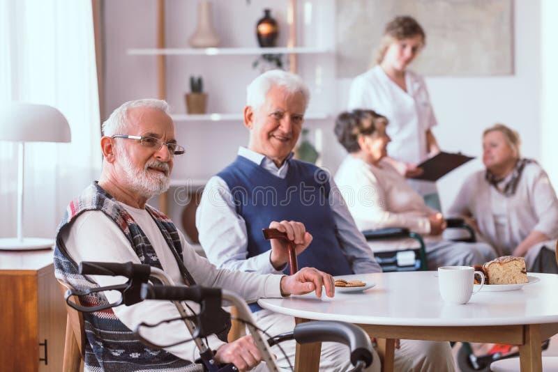 homme supérieur s'asseyant par la table dans la maison de retraite images libres de droits