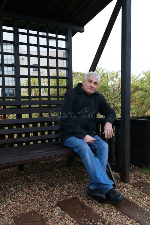 Homme supérieur s'asseyant sur le banc image stock
