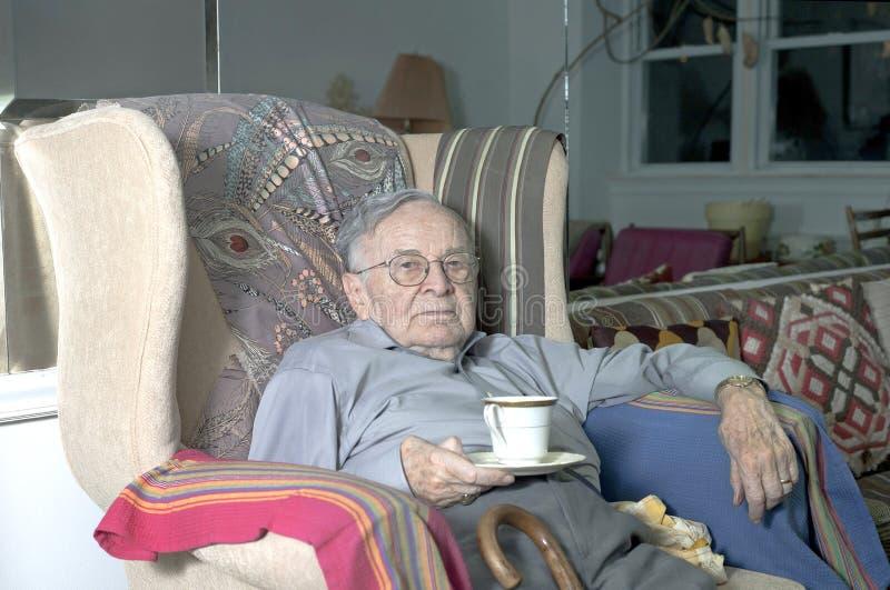 Homme supérieur s'asseyant sur le divan avec la tasse image libre de droits