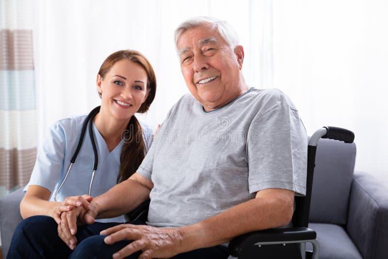 Homme sup?rieur s'asseyant sur le fauteuil roulant avec l'infirmi?re f?minine images stock