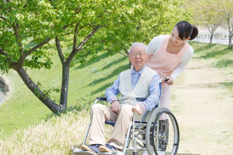 Homme supérieur s'asseyant sur un fauteuil roulant avec le travailleur social images stock