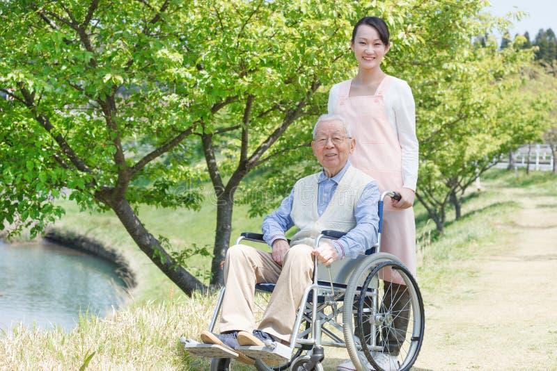 Homme supérieur s'asseyant sur un fauteuil roulant avec le travailleur social images libres de droits