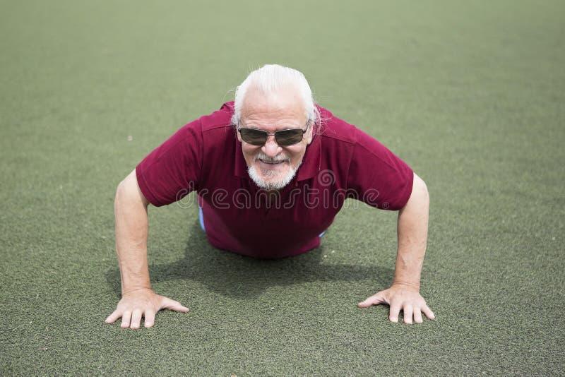 Homme supérieur s'exerçant dans un stade ouvert photos libres de droits