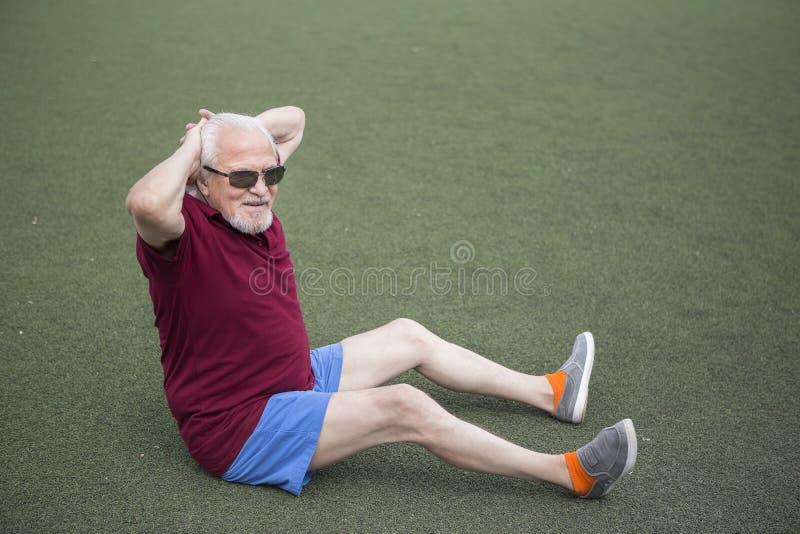 Homme supérieur s'exerçant dans un stade ouvert photo stock